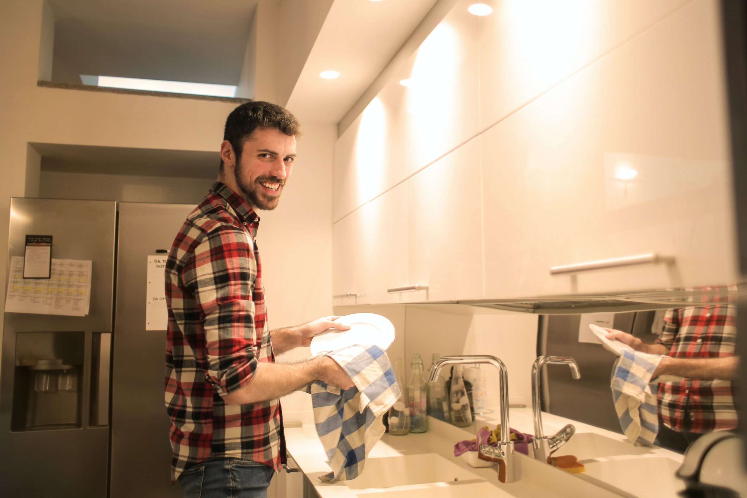 man wiping dishes in the kitchen