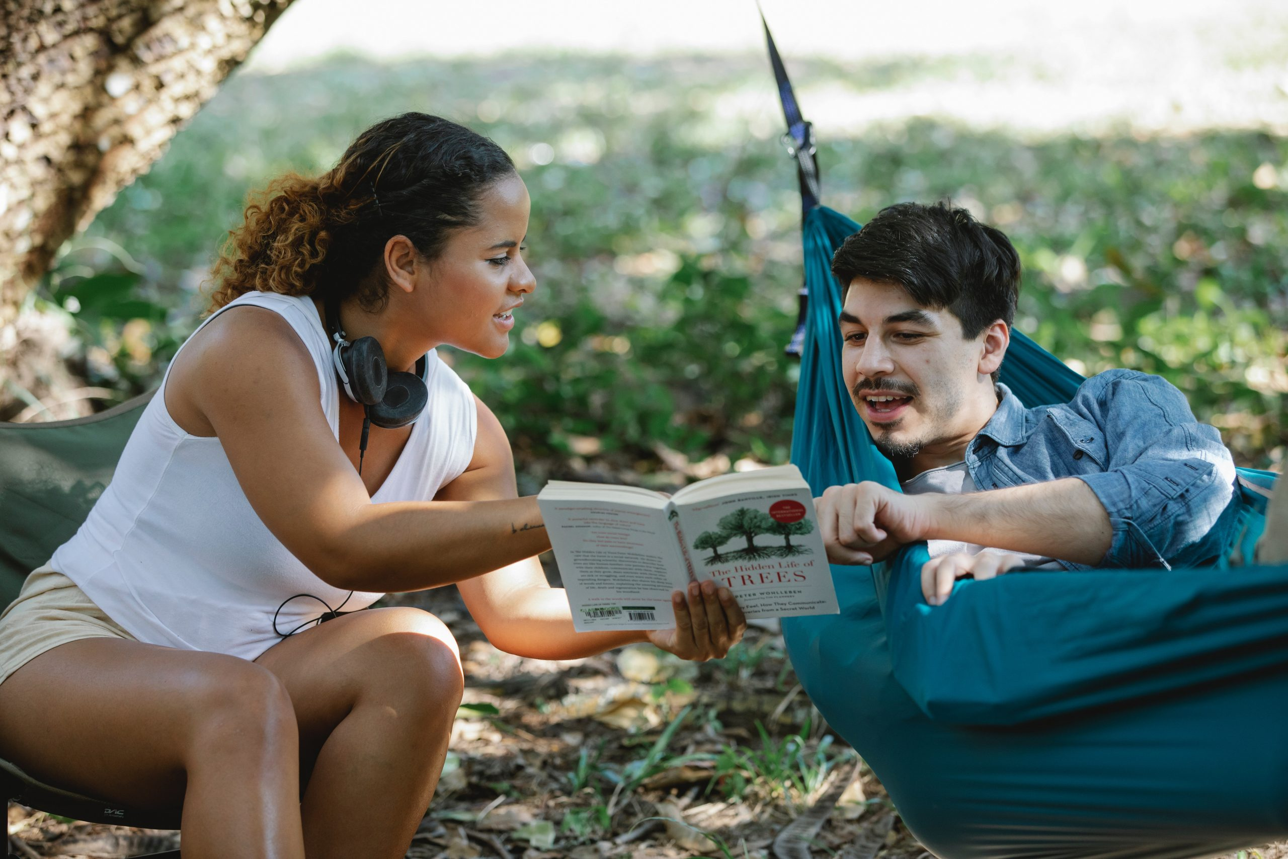 couple hanging out outside and talking about a book