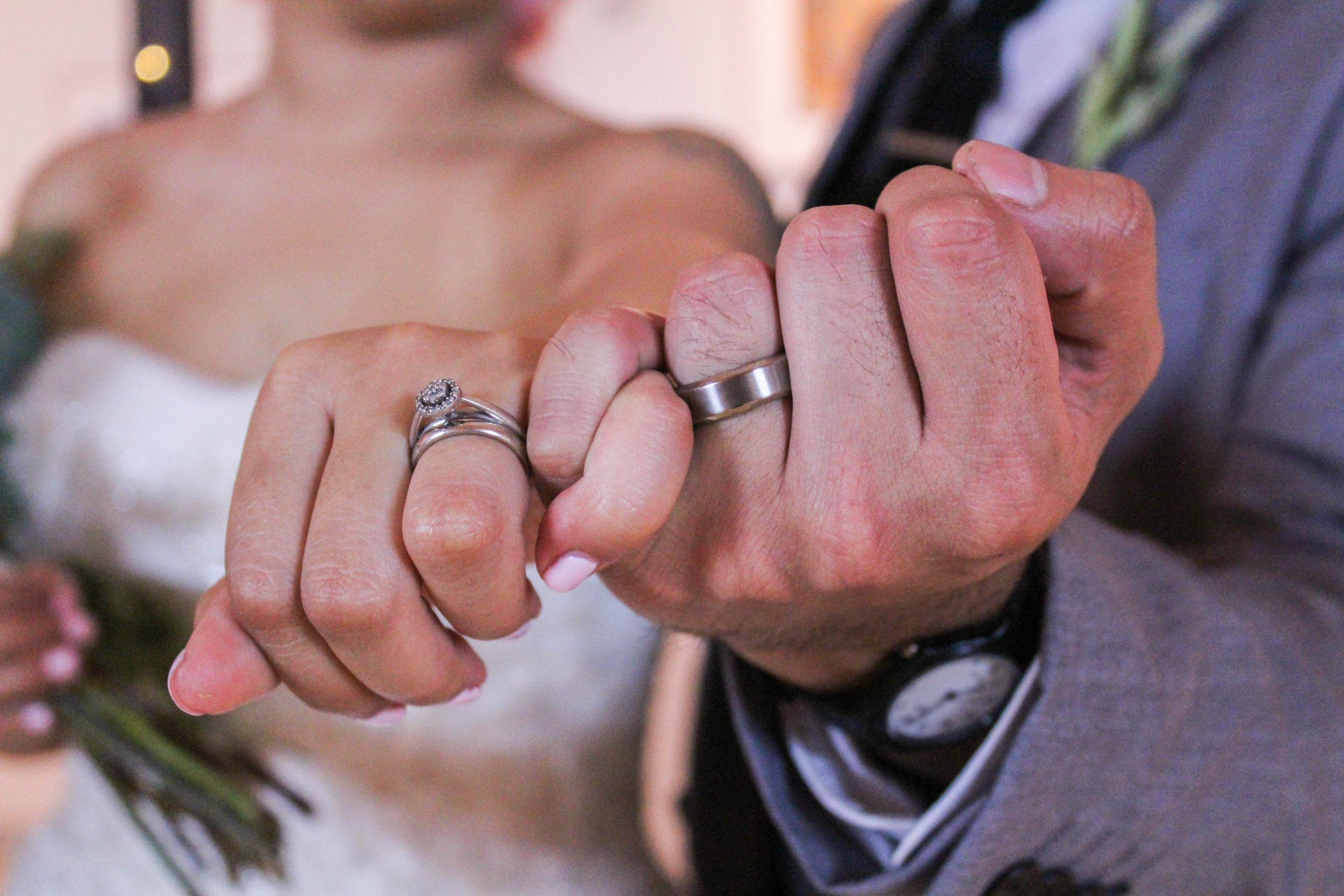 couple doing a pinky promise as they show wedding rings